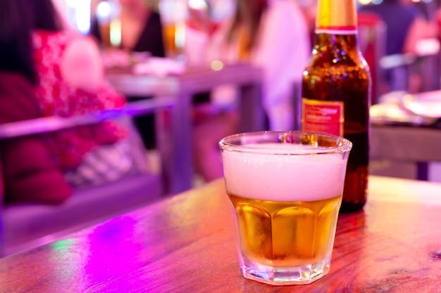 Bicchiere di birra con bottiglia in luci pazzesche estremamente colorate.