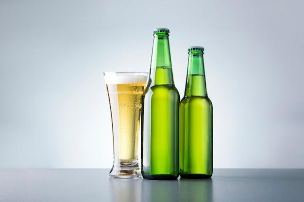 Bicchiere di birra con bottiglie su sfondo grigio. birra analcolica.