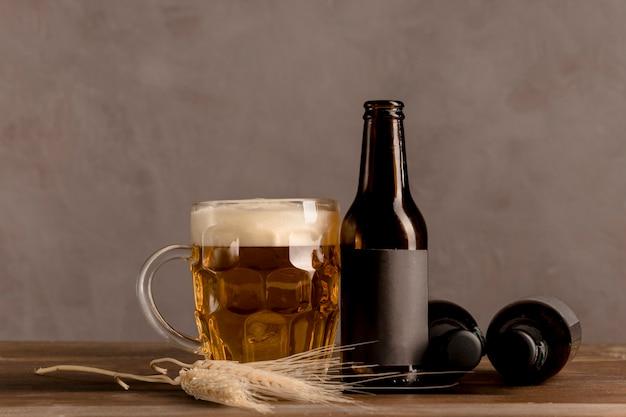 Bicchiere di birra con schiuma e bottiglie marroni di birra sulla tavola di legno