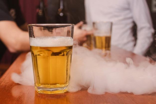 Un bicchiere di birra con fumo di vape in sottofondo al bar.