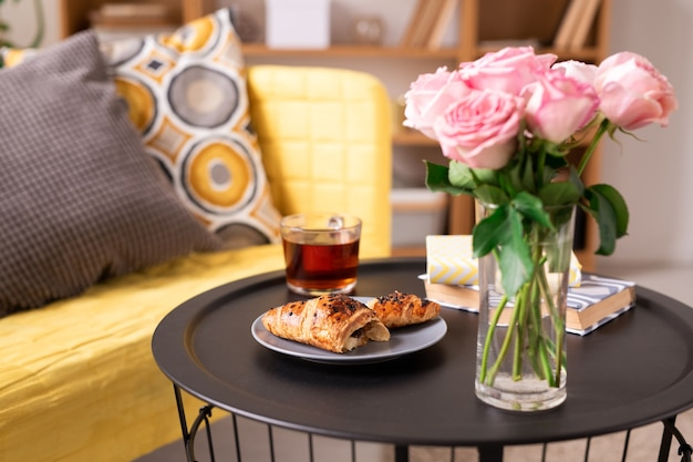 Bicchiere di tè nero, mazzo o rose rosa, croissant fatto in casa e due libri sul tavolino da divano in pelle gialla con cuscini