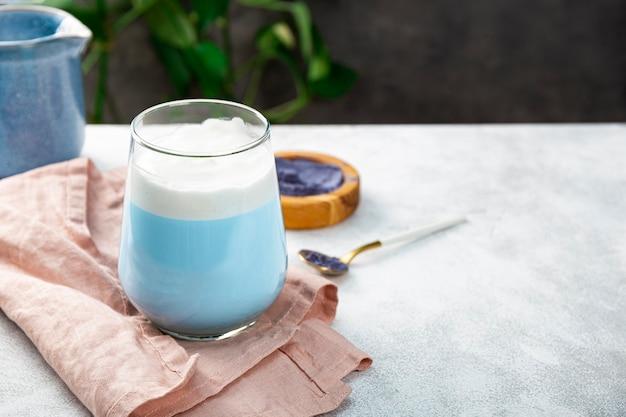 Un bicchiere di latte matcha blu nuovo superfood alla moda cibo sano spazio libero per il testo