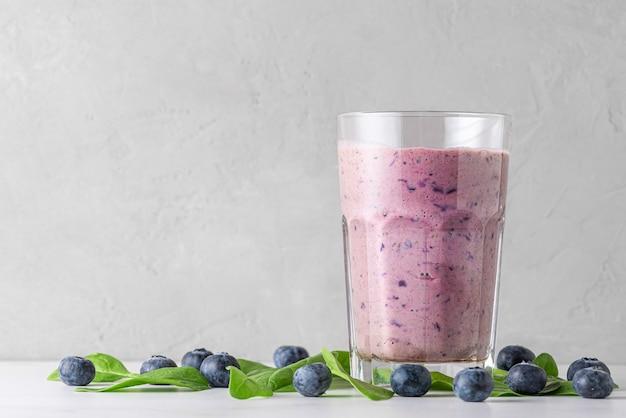 Bicchiere di frullato di mirtilli e spinaci o frappè con frutti di bosco freschi