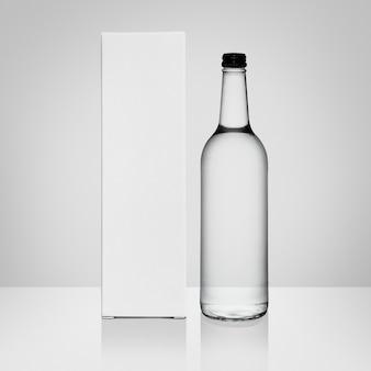 Bottiglia di vetro e scatola con copia spazio su sfondo bianco