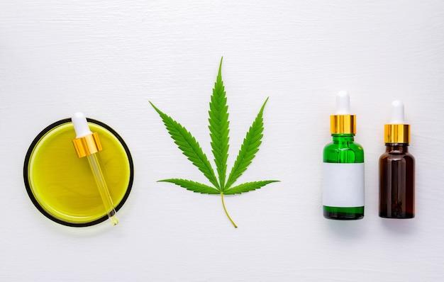 Bottiglia di vetro di olio di cannabis impostato su sfondo bianco.