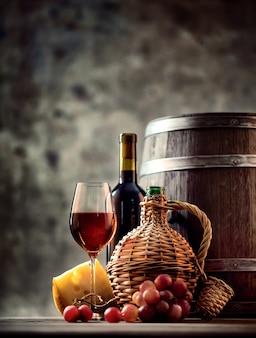 Bicchiere, bottiglia, caraffa di vino e botte
