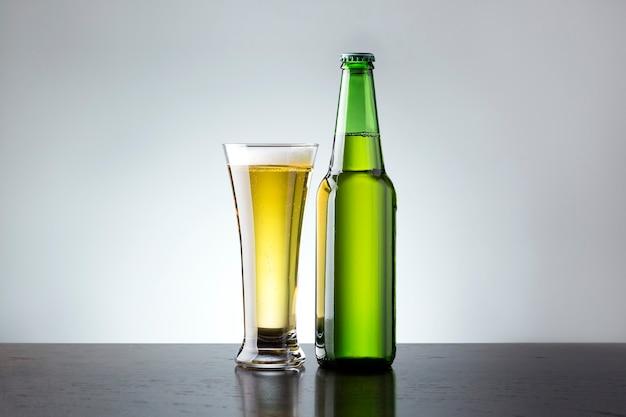 Vetro e bottiglia di birra fresca su sfondo grigio