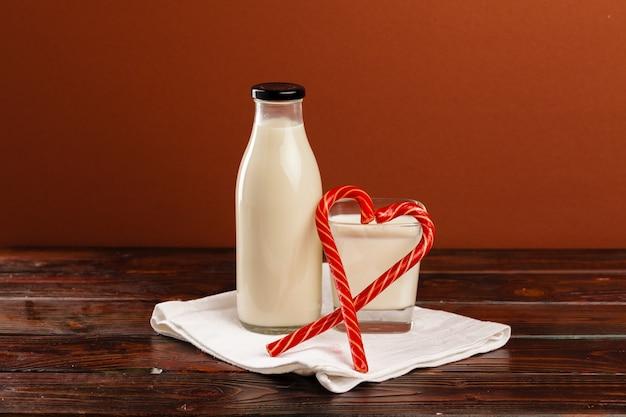 Bottiglia di vetro di latte fresco e bastoncini di zucchero sulla tavola di legno clsoe su