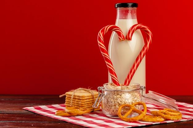 Bottiglia di vetro di latte fresco e bastoncini di zucchero sulla tavola di legno