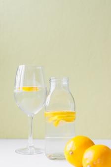 Bottiglia di vetro e calice di vetro con acqua e limone su sfondo chiaro