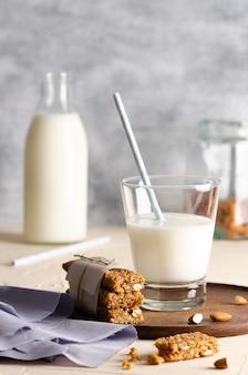 Un bicchiere e una bottiglia di latte con barrette di cereali alcune mandorle in un barattolo e un tovagliolo azzurro