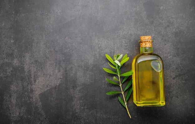 Bottiglia di vetro di olio d'oliva e ramo d'ulivo allestito su sfondo di cemento scuro.