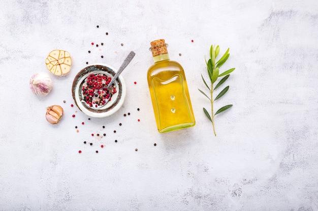 Bottiglia di vetro di olio d'oliva e ramo d'ulivo allestito su sfondo di cemento bianco.