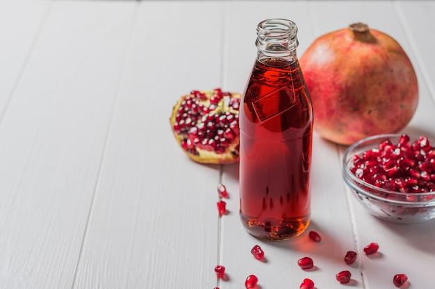 Bottiglia di vetro di succo di melograno con frutti di melograno maturi su un tavolo bianco. bere utile per la salute.