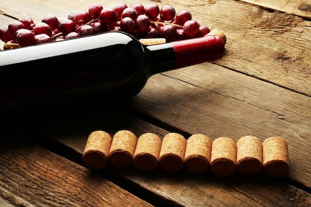 Bottiglia di vino in vetro con tappi di sughero e uva sullo sfondo della tavola in legno