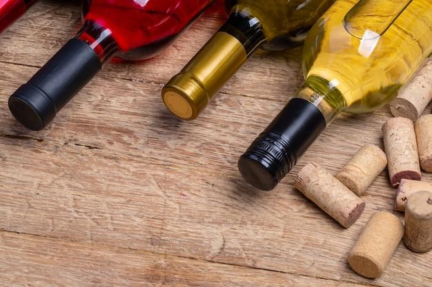 Bottiglia di vino in vetro con tappi di sughero sullo sfondo del tavolo in legno
