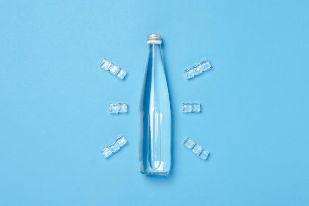 Bottiglia di vetro con acqua limpida su uno spazio blu con cubetti di ghiaccio. concetto di salute e bellezza, equilibrio idrico, sete, caldo, estate.