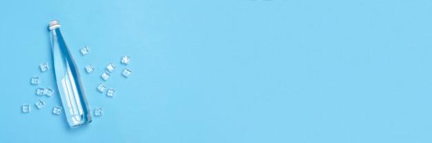Bottiglia di vetro con acqua limpida su un blu con cubetti di ghiaccio