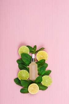 Bottiglia di vetro con prodotto cosmetico con metà di limoni, lime e menta su sfondo rosa, copia spazio