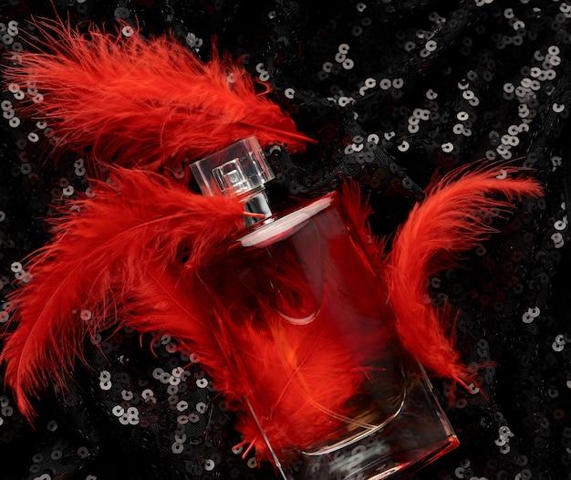 Bottiglia di vetro con liquido profumo rosa su sfondo nero con paillettes lucide e piume rosse
