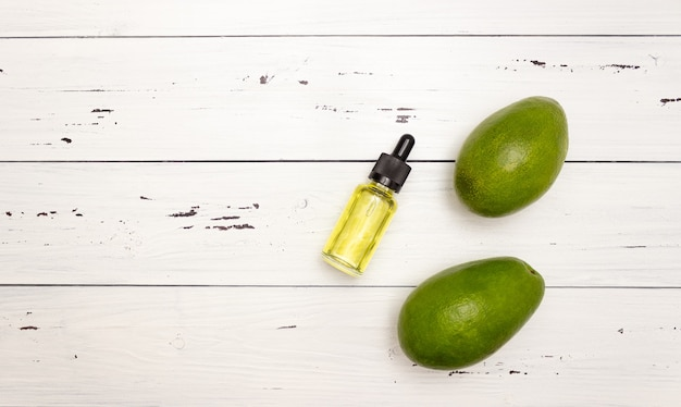 Bottiglia di vetro con pipetta e olio di avocado e frutto di avocado su uno sfondo di legno chiaro, vista dall'alto, spazio libero per il testo