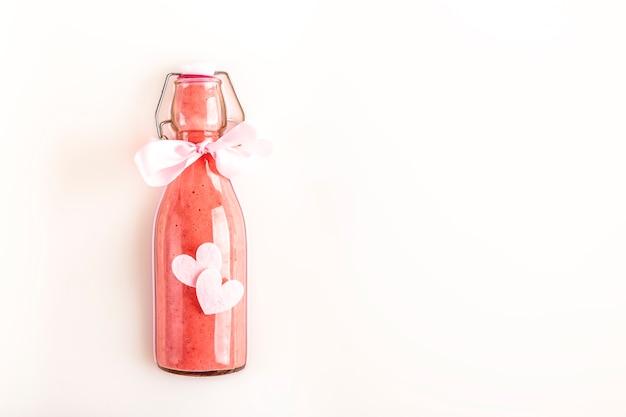 Bottiglia di vetro con frullato di fragole rosa rinfrescante sul latte con cuori adorabili e spazio di copia. concetto di cibo sano, disintossicante e dietetico. regalo.
