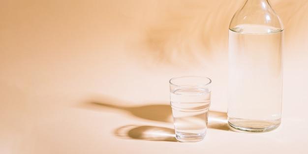 Vetro e bottiglia con acqua sulla superficie pastello