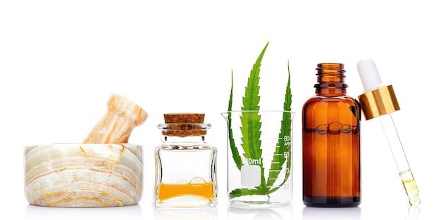 Bottiglie di vetro di olio di cannabis e foglie di canapa isolati su bianco. concetto di utilizzo della canapa in medicina.