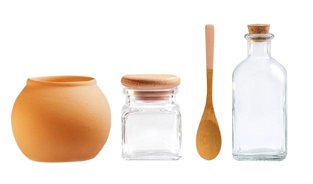 Bottiglie di vetro e utensili in ceramica su sfondo bianco