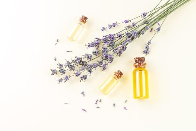 Set di bottiglie di vetro di olio essenziale di lavanda o profumo naturale con vista dall'alto di fiori di lavanda secchi. concetto di aromaterapia, cura della pelle, spa o massaggio