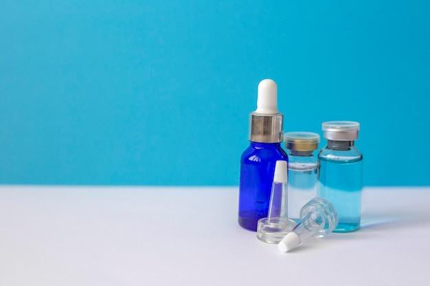 Le bottiglie di vetro con acido ialuronico stanno sul blu