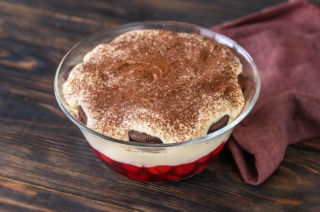 Ciotola di vetro di dessert con biscotti oreo, ciliegie e crema di formaggio