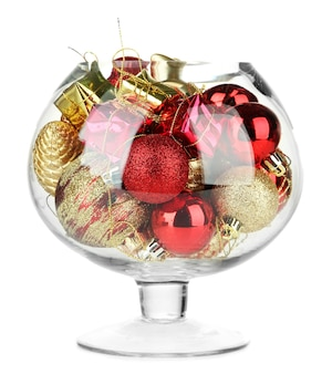Ciotola di vetro piena di decorazioni natalizie, isolata su bianco