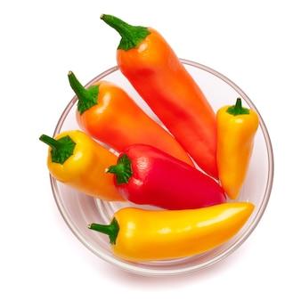 Ciotola di vetro piena di peperoncino o peperoni dolci isolati su superficie bianca