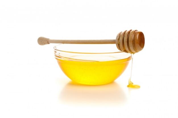 Ciotola di vetro di miele con mestolo isolato su sfondo bianco