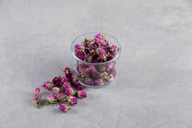 Ciotola di vetro di rose in erba viola poste su sfondo di pietra.