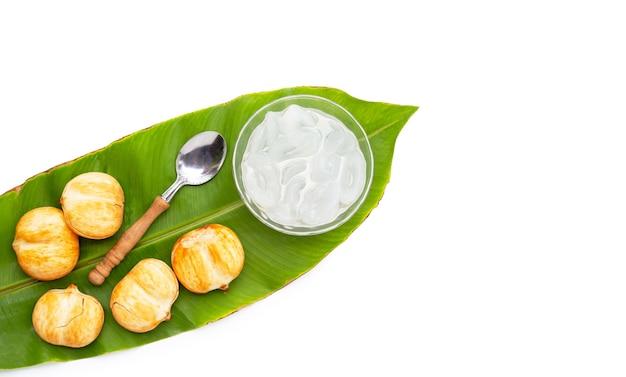 Ciotola di vetro di toddy palm affettato in sciroppo su foglie verdi su sfondo bianco.