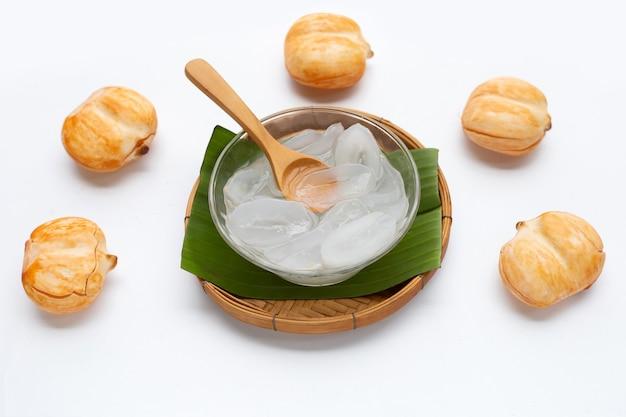 Ciotola di vetro di toddy palm a fette sciroppato su sfondo bianco.