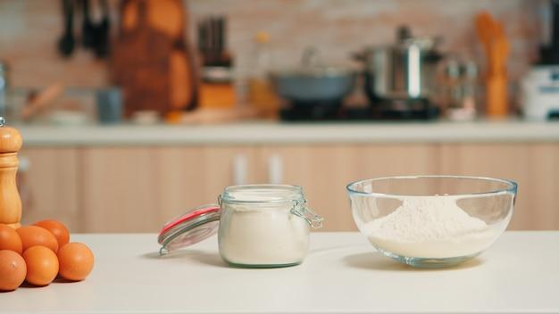 Ciotola di vetro di farina di frumento e uova fresche sul tavolo in cucina vuota. sala da pranzo moderna dotata di utensili pronti per cucinare con ingredienti di pasticceria per torte e pane fatti in casa