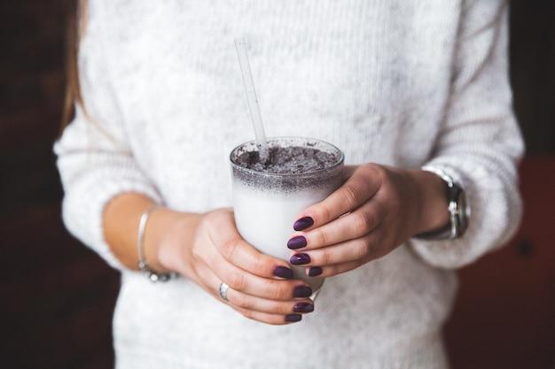 Ciotola di vetro con yogurt e nelle mani della donna. cibo, frappè