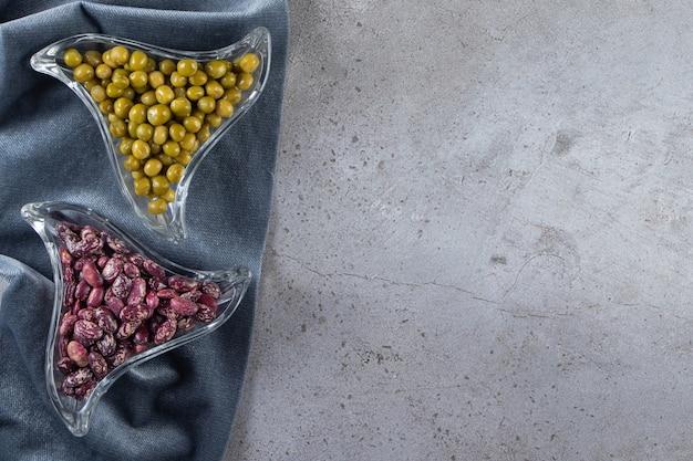 Ciotole di vetro piene di fagioli crudi e piselli su fondo di pietra.
