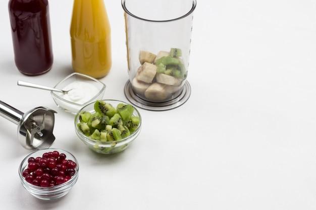 Ciotole di vetro con mirtilli rossi e kiwi. barattolo frullatore con banana. ingredienti per preparare frullati di frutta. vista dall'alto. copia spazio