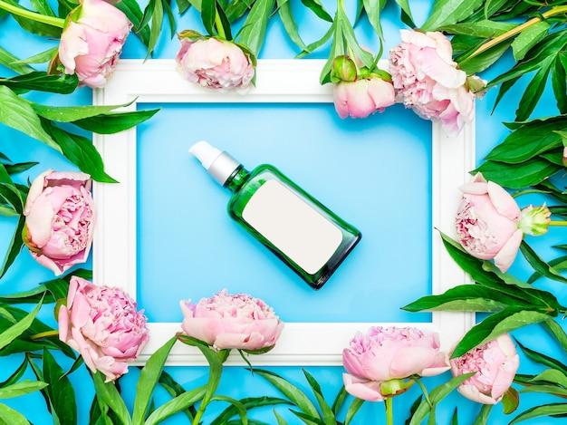 Bottiglia di vetro marrone con un'etichetta bianca circondata da peonie rosa, mockup del marchio cosmetico, piatto, copia spazio.