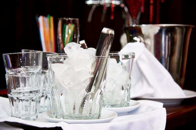 Secchio di vetro con cubetti di ghiaccio sulla barra.