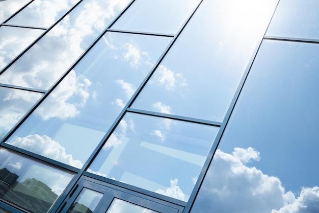 Facciata della costruzione di vetro con la riflessione del cielo blu