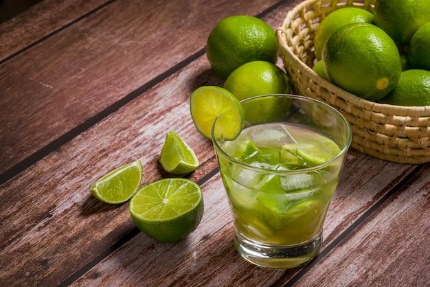 Bicchiere di caipirinha con limone su un tavolo di legno invecchiato tipico drink brasiliano