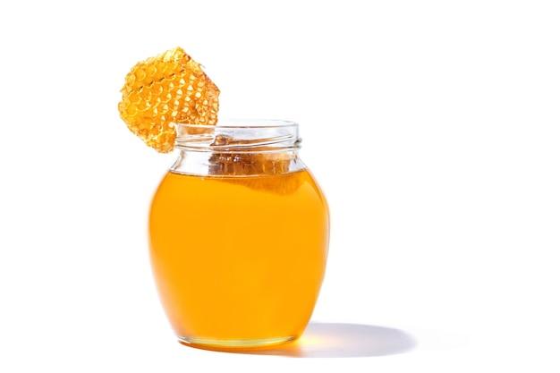 Lattina di vetro piena di miele e nido d'ape nel suo isolato su sfondo bianco.