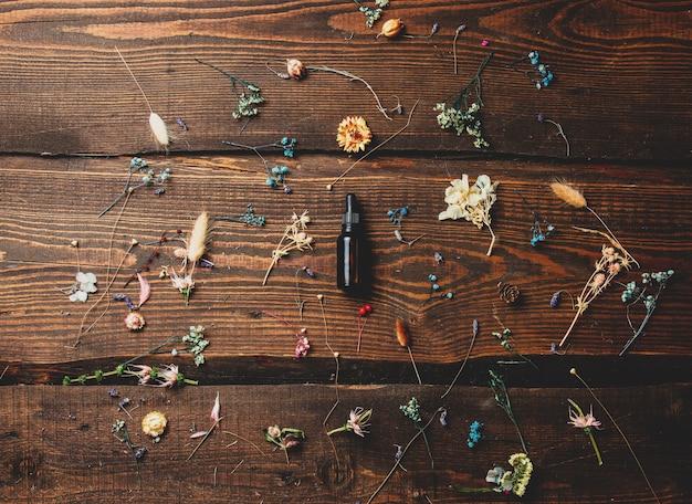 Capacità di vetro per olio cosmetico accanto a erbe secche sul tavolo di legno