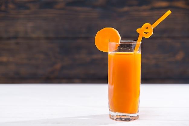 Bicchiere di succo di carota pieno di vitamine con paglia