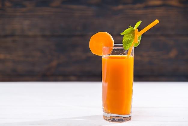 Bicchiere di succo di carota con foglia di menta sulla paglia
